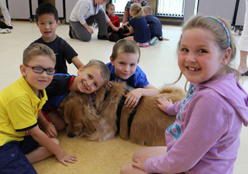 Students cuddle with therapy dog