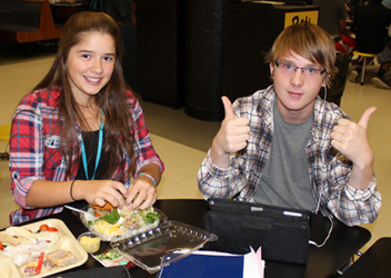 high school students in cafeteria eatting and giving a thumbs up